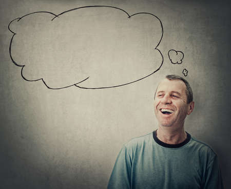 Happy middle age man laughing while looking aside and an empty thought bubble comes out of his head. Cheerful senior male smiling isolated on gray background. Positive emotions and thinking Фото со стока