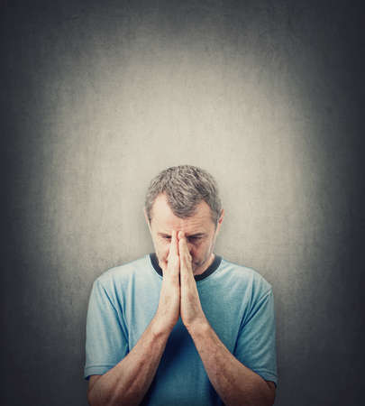 Depressed middle aged man praying over gray wall background with copy space above head. Senior male desperate looking down, keeps hands together as prayer. Concept of meditation, calming down