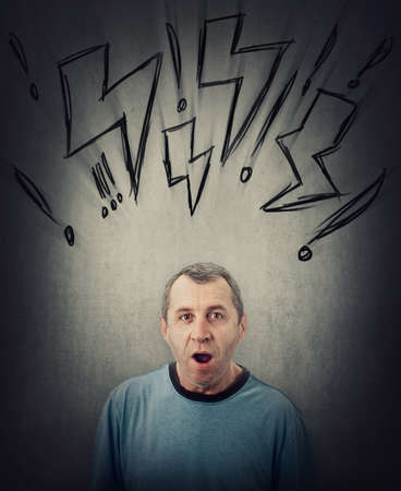 Shocked middle aged man looking with wide opened eyes and mouth isolated on gray wall background. Surprised senior male, astonished expression. Lightning sketches and exclamation marks above head Фото со стока