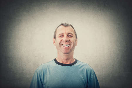 Happy middle age man smiling wearing casual t-shirt isolated over gray wall background. Portrait of cheerful senior male laughing overjoyed, positive emotions.