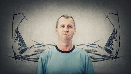Confident middle age man has no fears. Powerful senior male with biceps, muscular arms behind his back shows the inner strength. Super powers metaphor. Angry adult reacting annoyed Фото со стока