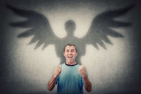 Courageous middle aged man keeps fists tight raised up, screaming showing his powers. Confident male casting a superhero shadow with angel wings on the wall. Inner strength and ambition concept Фото со стока