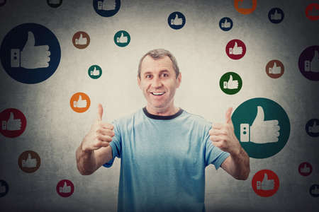 Excited middle aged man, shows thumbs up gesture, smiling contented to camera, surrounded by multicolor like signs. Senior male gives approval symbol, positive feedback, marketing concept Фото со стока