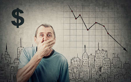 Shocked middle aged retired man, staring big eyes, covers his mouth with hand. Amazed and surprised due recession. Economic crisis concept, stock market financial graphs decrease. Business cessation