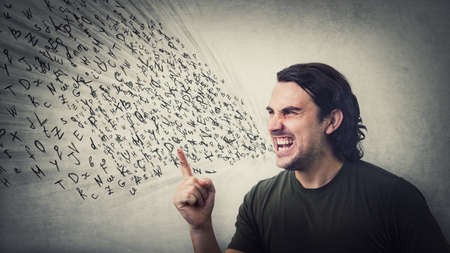 Angry man reacting furious clenching teeth screaming and shaking his index finger. Irritated and annoyed guy negative facial expression, blaming or scolding as multiple text letters come out his mouth