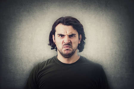 Bewildered and confused young man looking perplexed and upset to camera isolated on gray wall background. Angry casual guy, long curly hair style, irritated face, negative emotions.