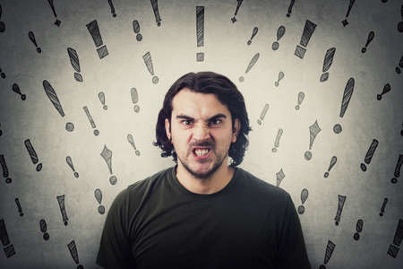 Bully man reacting furious, clenching teeth looking very angry with mad eyes to camera. Irritated and annoyed guy negative facial expression, blaming or scolding. Multiple exclamation marks sketches