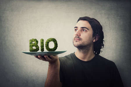 Young man waiter holding dish plate with Bio text made of green salad leaf. Healthy and organic food concept. Eco fresh crop nutrition, non GMO feeding. Vegan and vegetarian eating Фото со стока