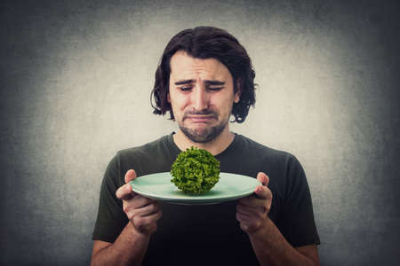 Desperate man crying as has only a lettuce batavia salad on dish plate. Dissatisfied vegan guy weeping as has little food to eat. Global crisis and hunger issue. Famine, starvation and malnutrition Фото со стока