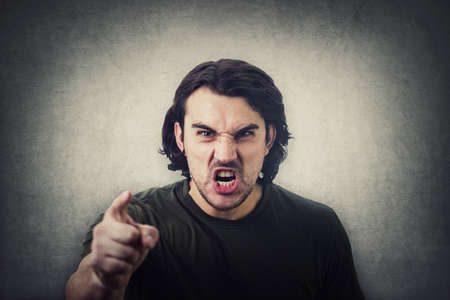 Furious young man pointing forefinger to camera blaming someone as guilty, or scolding isolated on gray wall background. Angry guy screaming and showing with index being annoyed