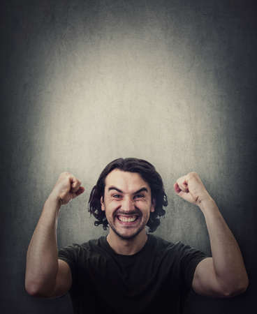 Pleased and positive man, long curly hair style, celebrates success hysterical and passionate. Guy keeps fists tight, raise hands up clenching teeth, isolated on gray wall with copy space above head Фото со стока