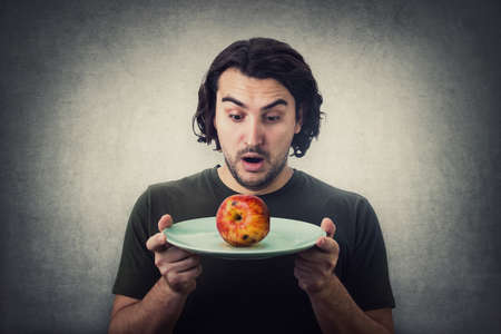 Shocked person holding dish plate a slightly degraded apple, rotten fruit. People has no food to eat after drought. Global crisis and hunger issue. Famine and starvation. Diet malnutrition concept Фото со стока