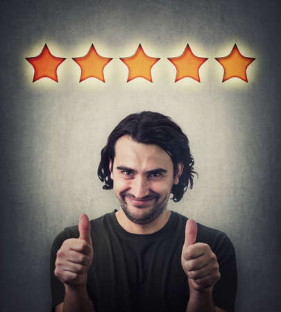Contented young man, shows both thumbs up gesture, slick smiling to camera. Attractive casual guy, happy emotion, gives like, approval symbol and five stars rating, positive feedback