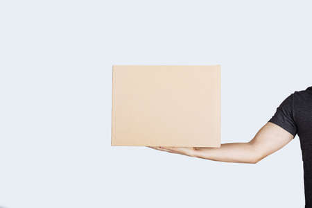 Delivery man hand holding package box isolated on white background. Courier Delivering Package Express Delivery Service. Фото со стока