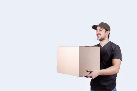 Image of a happy young delivery man with parcel post box isolated over white background. Courier delivering a package over white background. Excellent customer service concept. Фото со стока