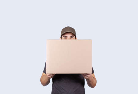 Happy delivery man holding a box package over gray background. Courier Delivering Package Express Delivery Service. Фото со стока