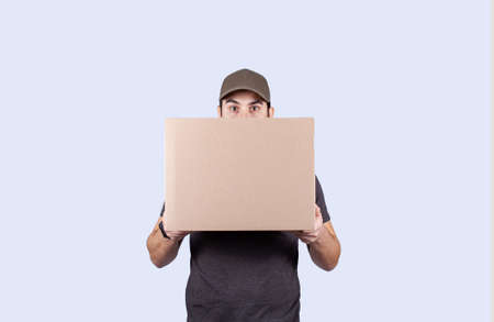 Surprised delivery man holding a box package. Shocked and astonished worker with wide opened eyes holding a box over gray background.