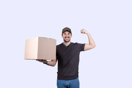 Happy delivery man holding a box package and felxing one hand biceps imagine superpower. Confident courier worker. Personal development, power and motivation concept.