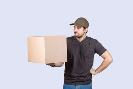 Confused Delivery man holding a box over white background. Don't know what to do. Courier doubtful and confused, with different options, wondering which decision to make. delivery concept