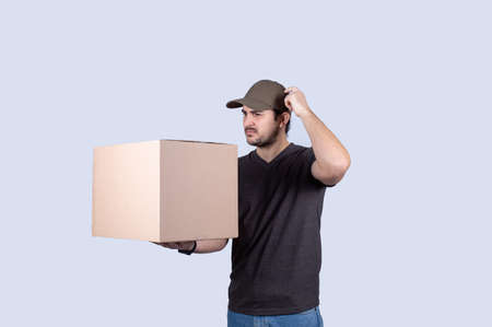 Pensive delivery man hand to head with thoughtful gesture, holding a box isolated on white background. Courier man holding box having problem with delivery over white background.