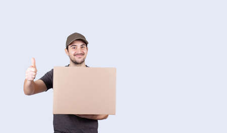 Portrait of happy delivery man holding a box package and showing thumbs up. Delivery man with a parcel showing thumb up for evaluating a good experience or service. Excellent customer service concept. Фото со стока