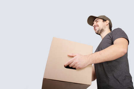 Image of a happy young delivery man with parcel post box isolated over white background. Courier delivering a package over white background.