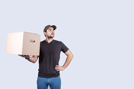 Delivery man holding a box package hands on hips showing chest, brave gesture keeps arms crossed confident, casting a superhero. Worker Ambition and business success concept. Leadership hero power, motivation and inner strength symbol.
