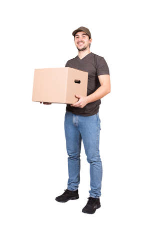 Cheerful delivery man looking to camera, full length portrait, holding a cardboard parcel box, isolated on white background. Happy courier delivering packages. Excellent customer service concept. 版權商用圖片