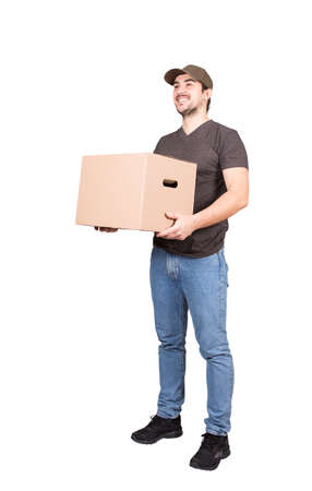 Cheerful delivery man wearing cap, full length portrait, holding a cardboard parcel box, isolated on white background. Happy courier delivering packages. Excellent customer service concept.
