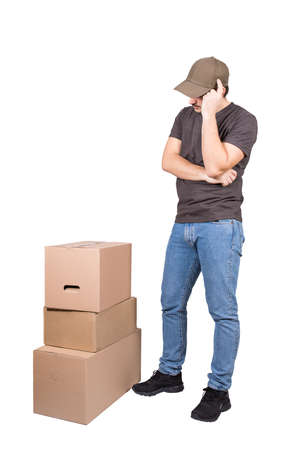 Thoughtful delivery man wearing cap, full length portrait, stands near cardboard parcel boxes, isolated on white background. Pensive courier delivering packages, thinking how to distribute quicker