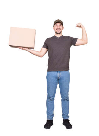 Confident delivery man, full length portrait, holding a cardboard parcel box and flexing his biceps muscles isolated on white background. Positive courier delivering package. Work motivation concept