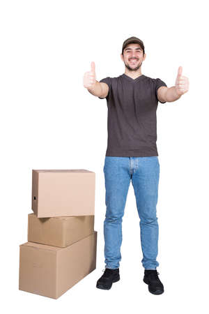 Contented delivery man wearing cap, full length portrait, shows thumbs up, stands near the parcel post boxes, isolated on white. Courier delivering packages. Excellent customer service concept. 版權商用圖片