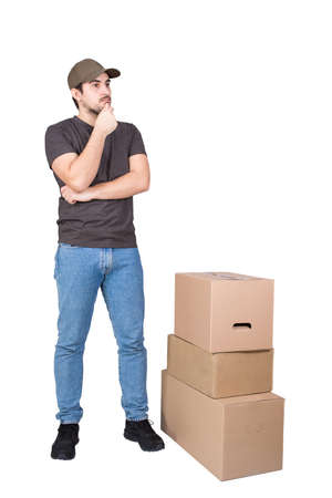 Thoughtful delivery man wearing cap, full length portrait, stands near cardboard parcel boxes, isolated on white background. Puzzled courier delivering packages, thinking how to distribute quicker