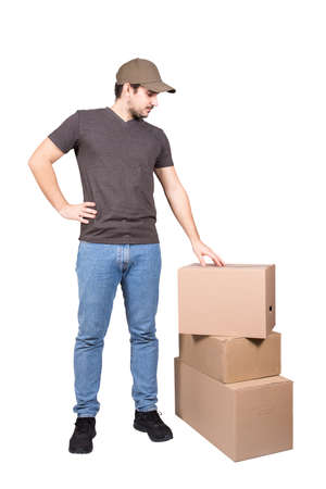 Thoughtful delivery man wearing cap, full length portrait, stands near cardboard parcel boxes, isolated on white background. Pensive courier delivering packages. Excellent customer service concept.
