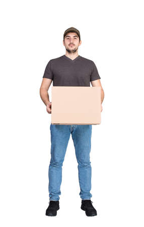 Serious delivery man looking to camera, full length portrait, holding a cardboard parcel box, isolated on white background. Confident courier delivering packages. Excellent customer service concept.