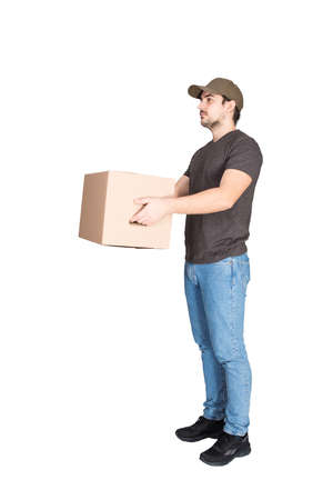 Responsible delivery man wearing cap, side view full length portrait, giving cardboard parcel box to customer, isolated on white background. Courier delivering package. Excellent service concept. 版權商用圖片