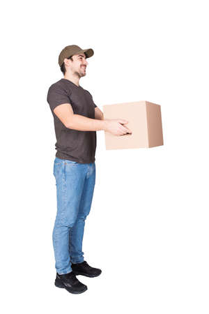 Cheerful delivery man wearing cap, side view full length portrait, giving cardboard parcel box to customer, isolated on white background. Courier delivering package. Excellent service concept.