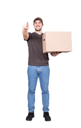 Joyful delivery man, full length portrait, carrying a cardboard parcel box pointing his forefinger to camera, isolated on white. Happy courier delivering package. Excellent customer service concept