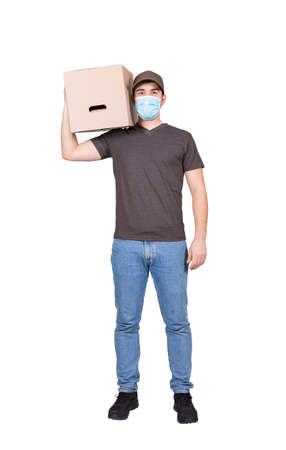 Healthy delivery man, full length portrait, wearing face mask as COVID-19 prevention measure, carrying a cardboard parcel box, isolated on white. Courier delivering package. Excellent customer service