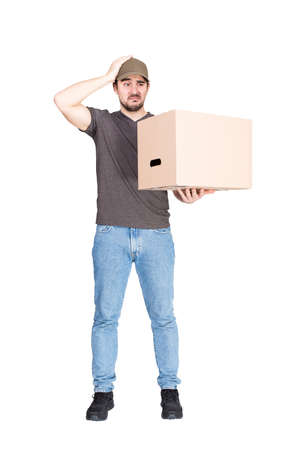 Confused delivery man, full length portrait, holding a cardboard box while keeps a hand to head, isolated on white. Puzzled courier has problems delivering package, messed up the parcels