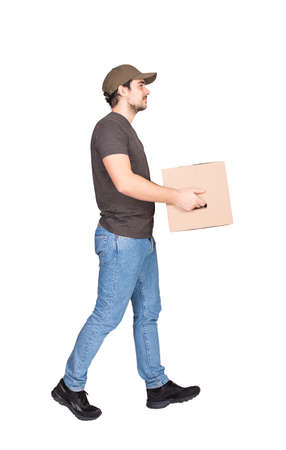 Side view delivery man on the move, full length portrait, walking and carrying a cardboard parcel box to customer, isolated on white background. Courier delivering package. Excellent service concept 版權商用圖片