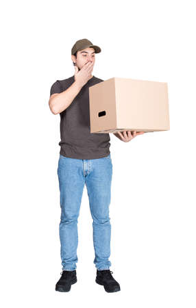 Shocked delivery man, full length portrait, holding a cardboard box while cover his mouth with hand, isolated on white. Astonished courier delivering package, messed up the parcels