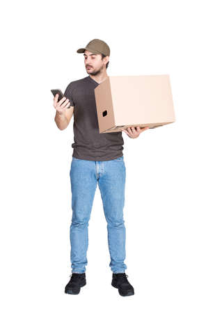 Delivery man, full length portrait, holding a cardboard parcel box while using his smartphone, isolated on white. Modern courier with phone delivering package. Excellent customer service concept 版權商用圖片