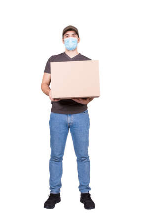 Full length delivery man holding a cardboard parcel box, wearing face mask as COVID-19 virus prevention measure, isolated on white. Postal courier manager delivering packages at home