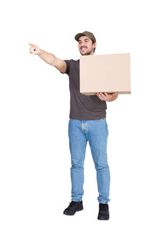 Joyful delivery man, full length portrait, carrying a cardboard parcel box pointing his index finger ahead, isolated on white. Happy courier delivering package. Excellent customer service concept
