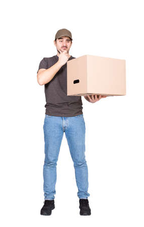 Doubtful delivery man, full length portrait, holding a cardboard box while keeps a hand under chin, isolated on white. Thoughtful courier has problems delivering package, messed up the parcels