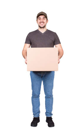 Positive delivery man, full length portrait, holding a cardboard parcel box in his hands, isolated on white background. Courier delivering package. Excellent customer service concept