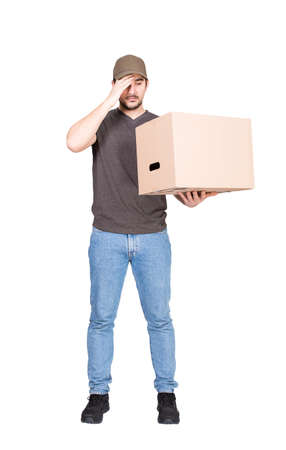 Confused delivery man, full length portrait, holding a cardboard box while keeps a hand to forehead, isolated on white. Puzzled courier has problems delivering package, messed up the parcels