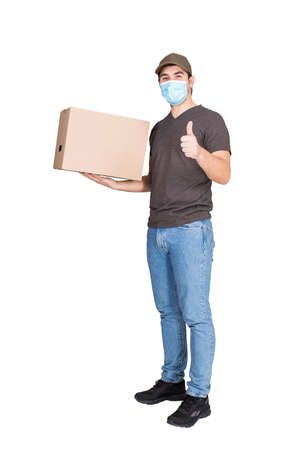 Cheerful delivery man, full length portrait, wearing face mask as COVID-19 prevention measure, carrying a cardboard parcel box, isolated on white. Courier delivering package shows thumb up gesture