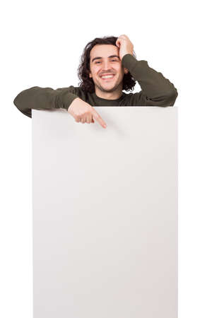 Positive man standing behind a blank banner for advertising and messages. Happy guy pointing his forefinger to the empty sheet, copy space for text announcements. Contented male, marketing concept
